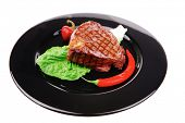 meat food : roast beef garnished with green lettuce and red chili hot pepper on black dish isolated over white background