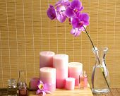 Pink branch orchid in glass with oil, candle on the bamboo background