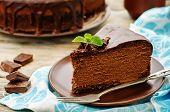 stock photo of cheesecake  - chocolate cheesecake with chocolate glaze on white wood background - JPG