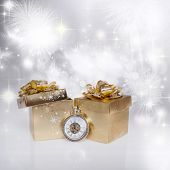 abstract holiday background with golden gift box, clock close to midnight and fireworks
