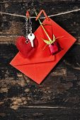 Red  envelop, key and rose  hanging on the clothesline. On old wood background
