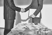 Two businessmen in formalwear handshaking after signing contract