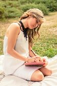 Romantic girl writing in a diary sitting outdoors