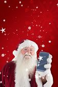 Santa Claus shows a smartphone against red snowflake background