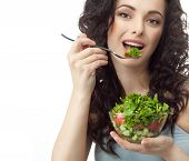 closeup portrait of attractive  caucasian smiling woman brunette isolated on white studio shot lips toothy smile face hair head and shoulders looking at camera eating salad