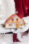 Santa holds a tiny house in his hands against blue