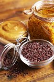 Mustard seeds and sauce in glass jar, bowls on wooden background