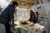 TAKAYAMA, JAPAN - DECEMBER 3, 2014: Local buys at a stall at the Miyagawa morning market in Takayama, Japan. This marketplace sells food items, groceries to farm produce and is common in rural Japan.