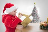Cute boy opening gift against christmas tree in bright room