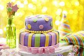 Delicious birthday cake on shiny yellow background