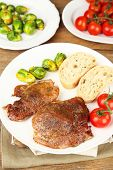 Roasted meat and vegetables on plate, on wooden table background
