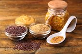 Mustard seeds, powder and sauce in glass jar, bowls and spoon on wooden background