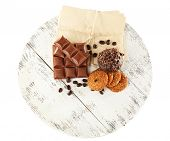 Pieces of chocolate with envelopes and cookies on wooden stand isolated on white