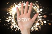Hand with fingers spread out against black and gold new year message