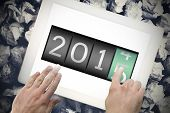 2014 changing to 2015 against hands touching tablet screen