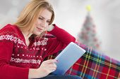 Woman using her tablet on the couch against blurry christmas tree in room