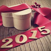 wooden numbers forming 2015, as the new year, a heart-shaped gift box and a red satin ribbon on a rustic wooden table