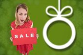 Surprised blonde showing a red sale poster against blurred christmas background
