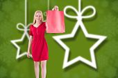 Pretty blonde in red dress holding shopping bag against blurred christmas background