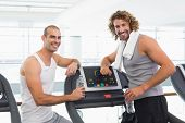 Portrait of a smiling male trainer and fit young man at the gym