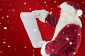 Santa Claus reads a list against red snowflake background