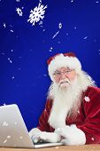 Santa surfs on the internet against blue snowflake background