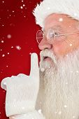 Santa claus making quiet sign against red snowflake background