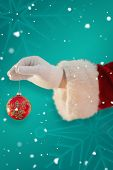 Santas hand is holding a Christmas bulb against green snowflake background