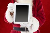 Santa claus showing tablet pc against red background