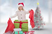 Cute girl in large gift against blurry christmas tree in room