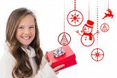 Girl holding gift against hanging red christmas decorations