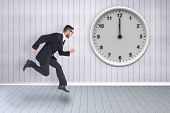 Geeky young businessman running mid air against grey room