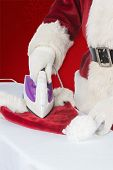 Father Christmas is ironing his hat against red background