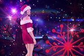 Pretty girl in santa outfit smiling at camera against digitally generated disco design on black