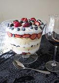 foto of sponge-cake  - Trifle dessert made with sponge cake whipped cream and berries accompanied by a glass of red wine - JPG