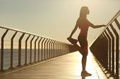 foto of stretch  - Woman silhouette exercising stretching on a bridge after running at sunset - JPG