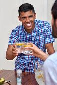 picture of gathering  - young cheerful man toasting with friends indoors at gathering - JPG