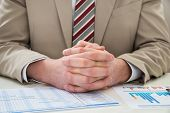 stock photo of employee month  - Close-up Of Businessman With Hands Clasped Over Gantt Chart ** Note: Shallow depth of field - JPG