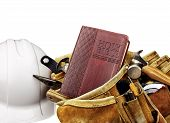 picture of carpenter  - Holy King James Bible and Carpenters Tool Belt with used tools and leather bags and white safety helmet on White Background - JPG