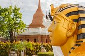 stock photo of pharaoh  - left side of golden pharaoh statue with brick pagoda background - JPG