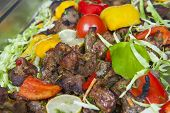 stock photo of veal  - Pieces of veal tandoori meat with salad on display at an indian restaurant buffet - JPG