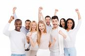 stock photo of casual wear  - Group of happy young people in smart casual wear looking at camera and keeping arms raised while standing against white background - JPG