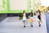 foto of girl walking away  - Girls holding shopping bags and walk around the shops - JPG