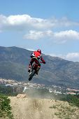 image of moto-x  - orange and red moto x or moto cross bike jumping over hump on dirt track in sunny marbella with mountain backdrop - JPG