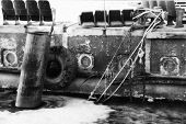 stock photo of barge  - A side of an old barge with ropes, pipe, ice and tire. ** Note: Soft Focus at 100%, best at smaller sizes - JPG