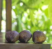 stock photo of green snake  - Snake Fruit and Green Leaf on the Wood Table - JPG