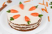 picture of sponge-cake  - Tasty easter sponge cake with cream and little carrots on top on white plate background - JPG
