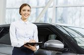 stock photo of showrooms  - Young pretty woman dealer in showroom standing near car  - JPG