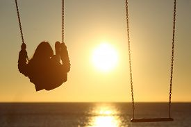 foto of swing  - Back light of a lonely woman silhouette swinging at sunset on the beach with another empty swing - JPG