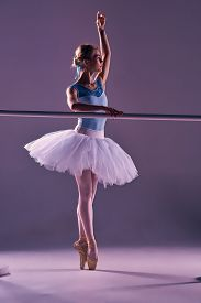 image of ballet barre  - classic ballet dancer in white tutu at ballet barre on a lilac background - JPG